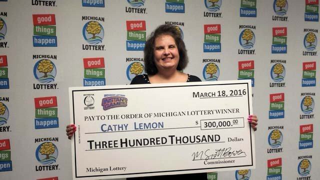 Cathy Lemon holding check after winning $300,000 (Source: Michigan Lottery)