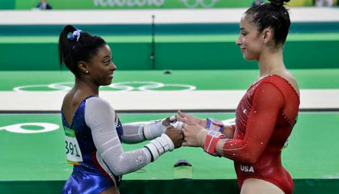 United States' Simone Biles, left, and Aly Raisman encourage each other during the artistic gymnastics women's individual all-around final at the 2016 Summer Olympics in Rio de Janeiro, Brazil, Thursday, Aug. 11, 2016. (AP Photo/David Goldman)