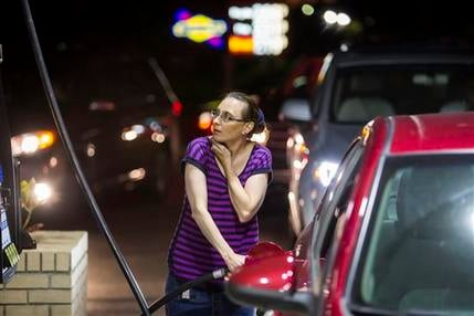 Beth Johnson fills up her car after waiting in line at a Sunoco gas station in advance of Hurricane Matthew in Mt. Pleasant, S.C.,