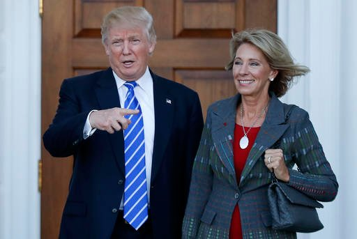 (AP Photo/Carolyn Kaster, File). In this Nov. 19, 2016, file photo, President-elect Donald Trump and Betsy DeVos pose for photographs at Trump National Golf Club Bedminster clubhouse in Bedminster, N.J.