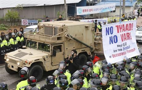 U.S. military vehicle moves past banners opposing a plan to deploy an advanced U.S. missile defense system called Terminal High-Altitude Area Defense, or THAAD, as South Korean police officers stand guard in Seongju, South Korea