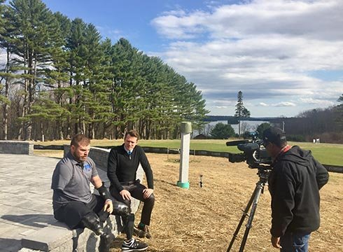 David Custer sits with Travis Mills at his Maine retreat. (Source: WNEM)