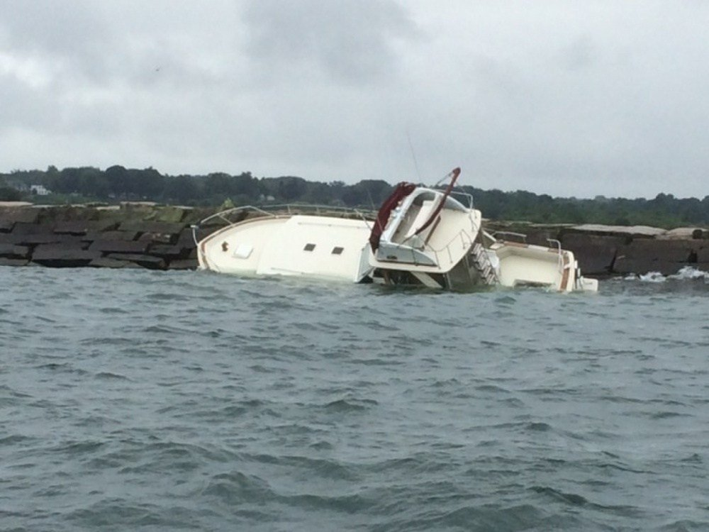 A 38-foot pleasure craft sits atop of the east breakwall inside Conneaut Harbor, Conneaut, Ohio, July 23, 2014. The responsible party has established a salvage plan. (U.S. Coast Guard photo)