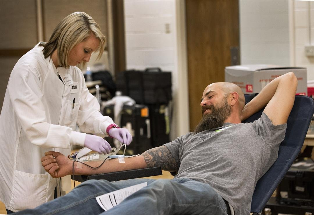 American Red Cross collections staff member Cherrelle Simon collects a blood donation from Clint Kraft. Clint says that he gives blood because his wife suffers from a rare disease. (Source: Red Cross)