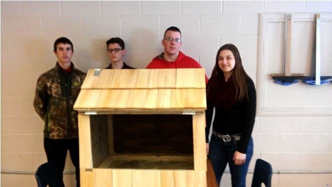 The main Baraga Area Schools student workers who completed the nest box build, from left, Zach Sackett, Caleb Hansen, Alan DesRoucher, and Lacey Sterbenz, stand with their completed project. (John Filpus photo)