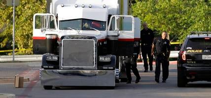 San Antonio police officers investigate the scene where eight people were found dead in a tractor-trailer loaded with at least 30 others outside a Walmart store in stifling summer hea