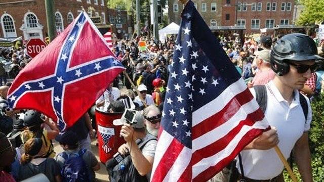 (AP Photo/Steve Helber). White nationalist demonstrators walk into Lee park surrounded by counter demonstrators in Charlottesville, Va., Saturday, Aug. 12, 2017.