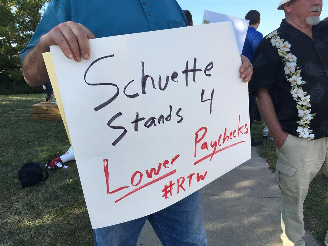 Protesters stand outside the barbecue where AG Schuette is expected to announce his run for governor. (Source: WNEM)
