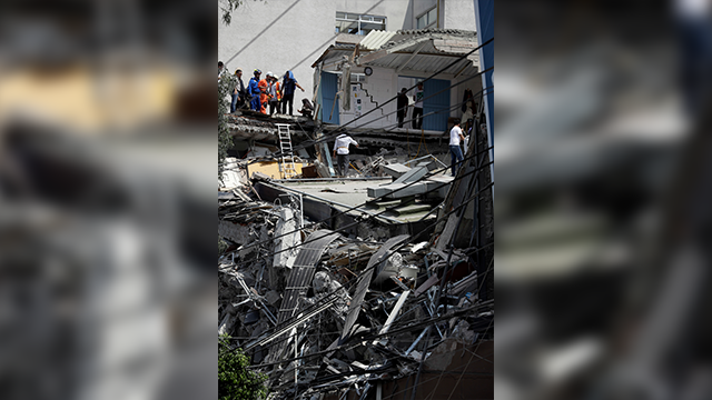 Rescue workers and volunteers search a building that collapsed after an earthquake in downtown Mexico City
