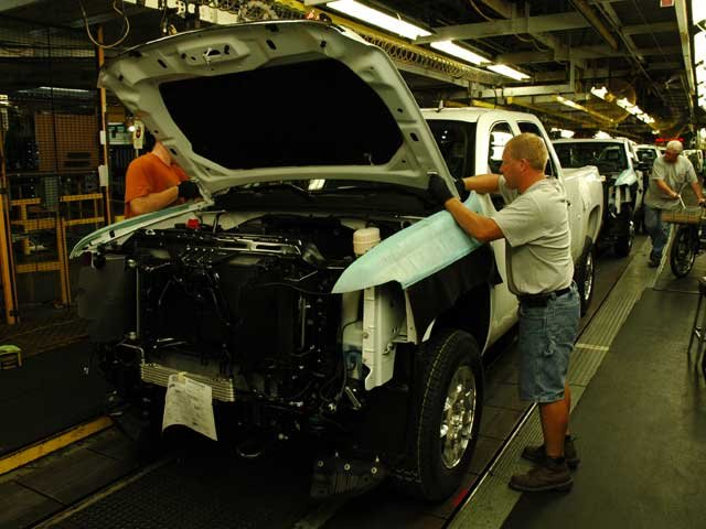 Tom Christensen of Essexville installing a hood on a truck as it travels down the final line at Flint Assembly. Christensen has worked at the plant since 2006.