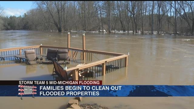 Families begin to clean out flooded properties