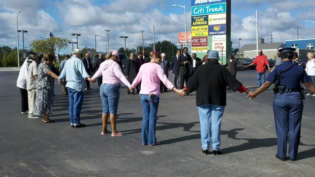 Citizens gathering to pray at the site where Milton Hall was shot to death.
