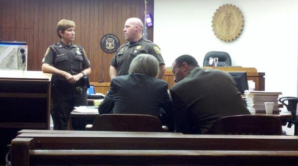 Ken Bluew talking with his attorney during a break in proceedings.