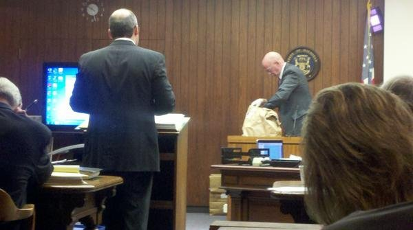 Ogg in court opening a laundry bag containing Bluew's uniform.