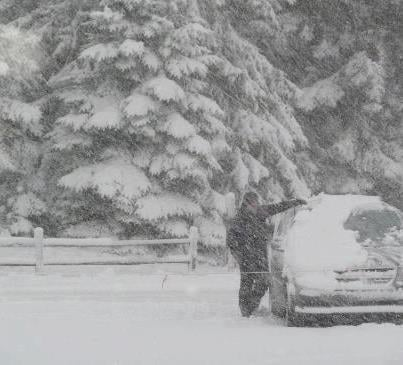 A person clears snow off a car in a Northern Michigan county.
