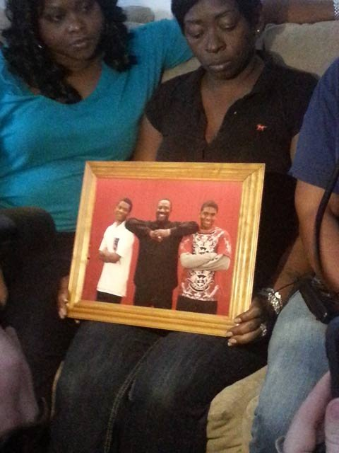 Family members holding a photo of the teen who died New Year's Day.