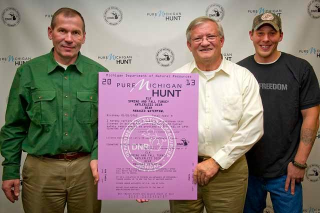 From left to right, 2013 Pure Michigan Hunt winners Jim Bosscher, Dave Gittins and Jason Webb with hunting license.