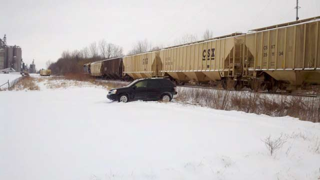 The driver's Chevy Equinox in the snow near the train.