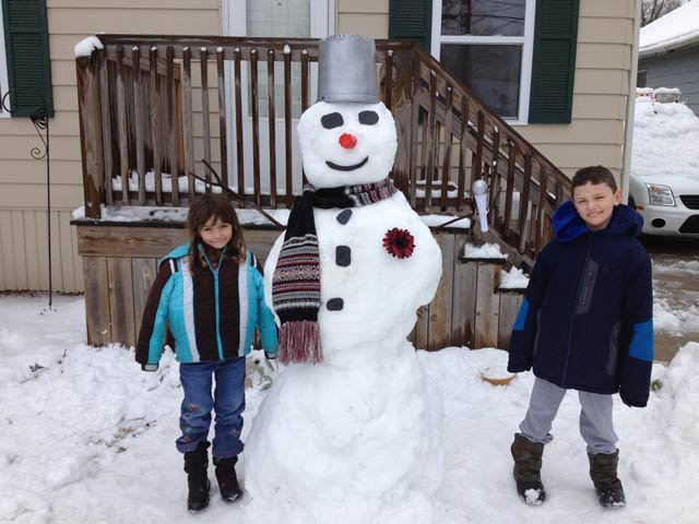 This photo shows Julia, 5, and Chase, 7, next to the snowman they built -- notice the microphone in his hand for TV5.