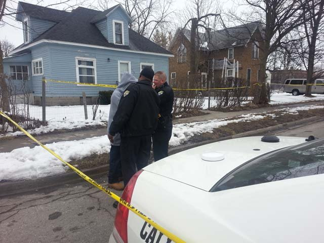 Police talking to a family member outside the home where two bodies were found.