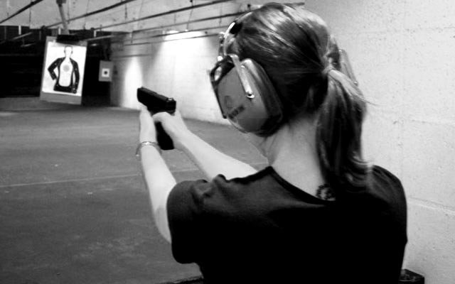 A woman shooting at a gun range.
