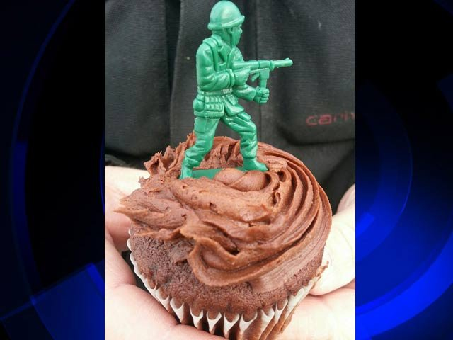 A soldier adorning a chocolate cupcake.