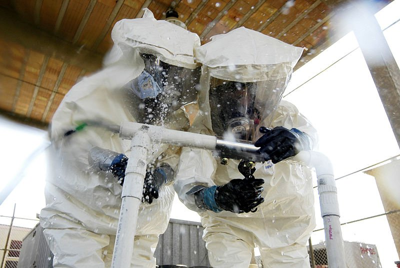 This stock photo shows two people inside hazard suits.