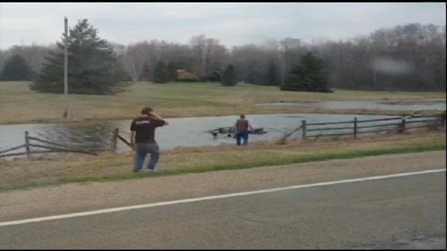 A photo from the video showing the men running at the car in the pond.