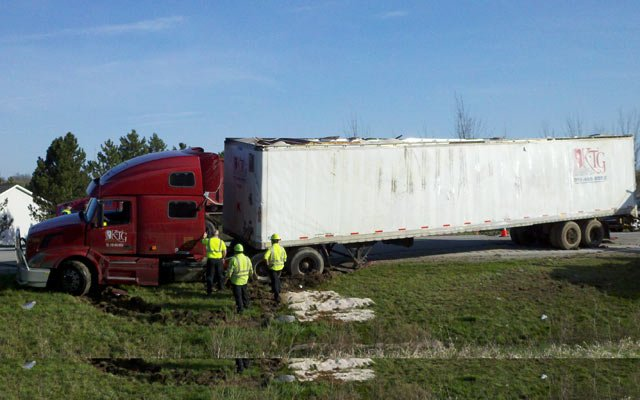 A side view of the truck where it ran off the highway -- the trailer has been set upright.