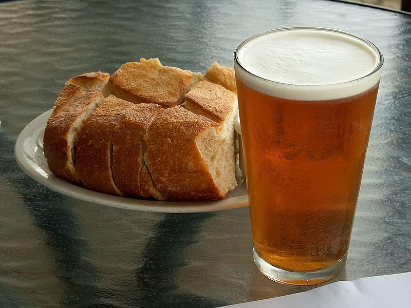 A pint of fresh beer with a side of bread.