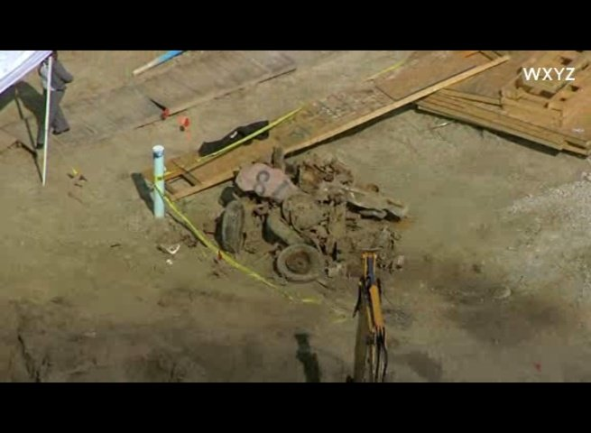 A view of the dig scene where car parts have been excavated and placed in a pile.