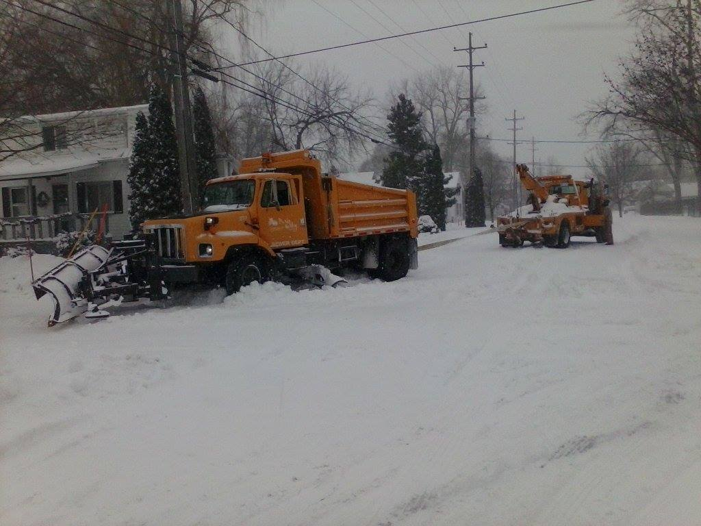 A plow truck gets help from a tow truck on Monday in Mid-Michigan.