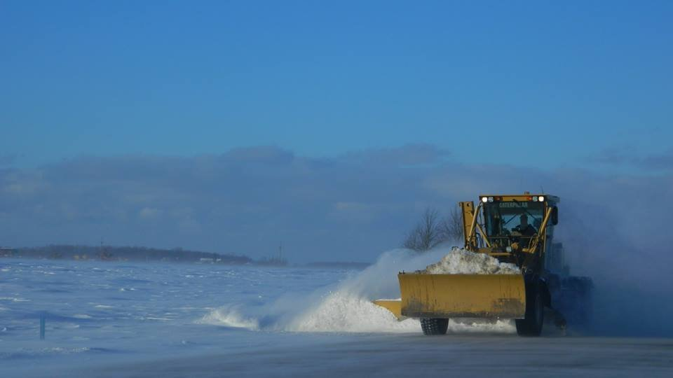 A road grader moving snow in the Thumb.
