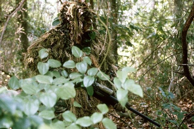 A man in a 'ghillie' suit.