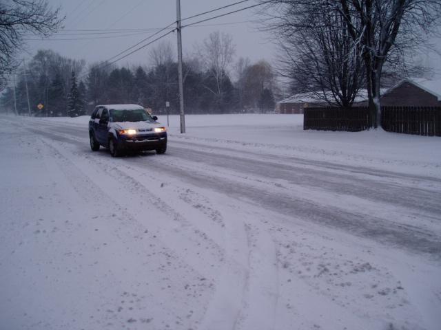 A car driving down a Saginaw Township road in deep winter.
