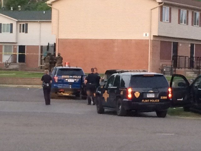 Police in a standoff with possible murder suspects.