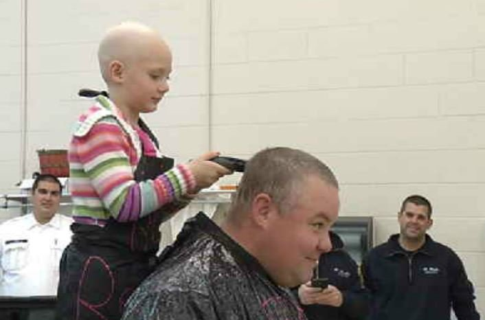 Brinley shaves a man's head as part of the Brinley's Bald Head Challenge in October 2015.