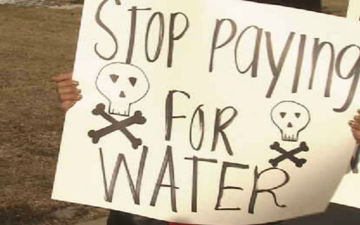 Flint residents hold signs protesting their water bills. (Courtesy WNEM)
