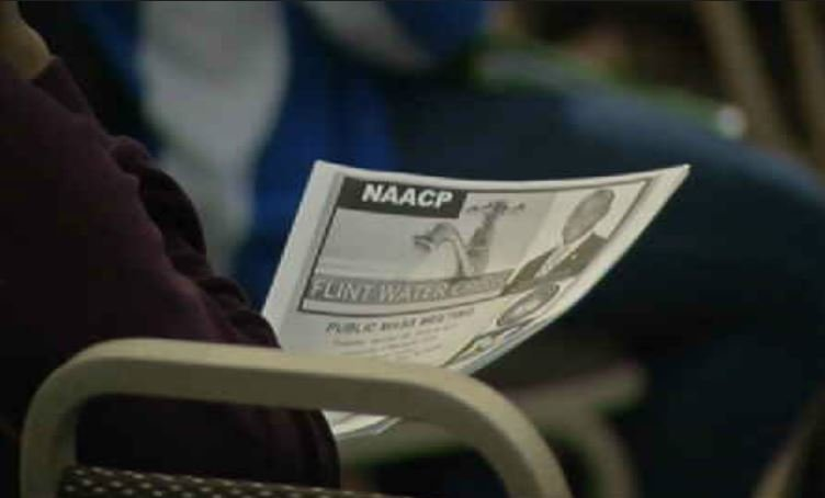 A Flint resident looks over a program at an NAACP town hall.