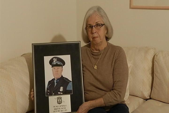 Pat Butterfield holds a photo of her deceased son who was killed in the line of duty. (Sourcre: WNEM)