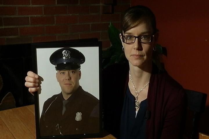 Erin Wolf holds a photo of her husband Chad Wolf. The Michigan State trooper died while on duty. (Source: WNEM)